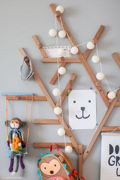 Quarto infantil com estilo escandinavo tem cabideiro no formato de árvore.