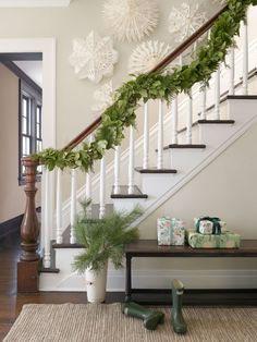 Instead of a single-note pine decorating the staircase of this Connecticut farmhouse, the owners opted for an intricate FiftyFlowers garland that incorporates fresh asparagus ferns and evergreen shrubs.   - CountryLiving.com