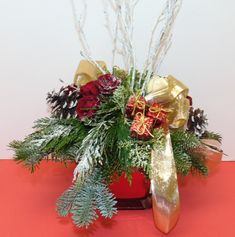 This holiday arrangement is sure to add some holiday cheer to your home or office! #florist #flowers #flowershop #centerpiece #florals #flowerarrangement #floralarrangement #roses #carnations #pinecones #berries #candles #holidays #christmas #greens #flowersoftheday #flowerlover #flowerlovers #flowerpower #blooms