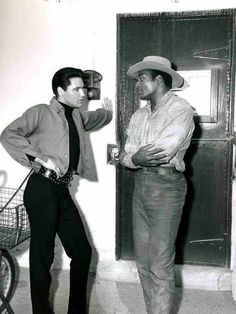 Elvis chating with football player Jim Brown between take on the set of Roustabout in spring 1964.