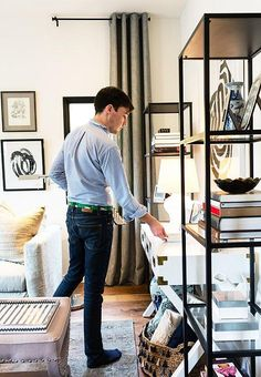 Alex makes some final adjustments to black iron open bookshelves that have been styled with coffee table books, Chinoiserie ginger jars and souvenirs from travels around the world. See more from our Honestly WTF Home Tour and Modern Living Room Makeover with The Studio at One Kings Lane: Inside Blogger Erica Chan Coffman's Oakland, CA Pad over on our Style Guide!