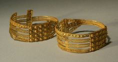 ETRUSCAN GOLD FILIGREE EARRINGS  Openwork ribbons filled with wire bands, bosses, scrolls. Probably from Vetulonia  Ca. 1st 1/4 of the 7th Century BC  Dia. 1 9/16 in. (4 cm.) Weight 4.1 gms., 4.3 gms.  Ex Thane Collection, England.