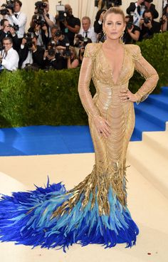BLAKE LIVELY wearing a golden Atelier Versace gown with epaulets and an exuberant blue ombré feather fringe train.