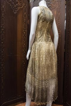 1920s Silver Lamé Lace Dress. This piece is incredibly rare, constructed from silver lamé lace threads and original cream-beige silk interior scaffolding. The piece is gusseted past the hips with snaps all the way down from arm to hip. The hem is raised in the front and graduates down in the back. Sideway back