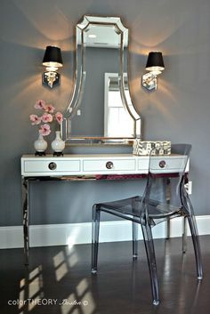 Gorgeous dressing area with Jonathan Adler Channing Three-Drawer Console Table paired with an Uttermost Cattaneo Silver Beaded Mirror flanked by octagonal nickel wall sconces with black shades against a backdrop of dark gray walls with a smoke gray acrylic chair in front over hardwood floors.