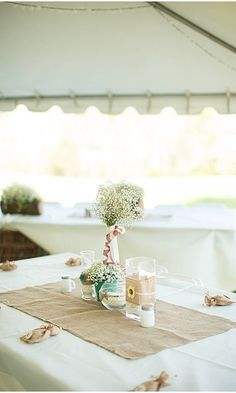 A twist on burlap table decor. Rectangle cloth under centerpiece with touches of burlap.