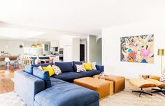 Navy sectional in living room with Eames chair, artwork, and leather benches/coffee table