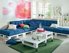 White pallet table and pallet sofa with blue pillows.
