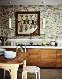 amazing stone wall with custom cabinetry in reclaimed wood. The simple modern pendants and sleek corian (?) countertop really set off the rustic vibe of the rest of it. via decorology