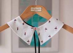 White pointed Peter Pan collar featuring small pinups. With a maritime button on the front and hook closure on the back.
