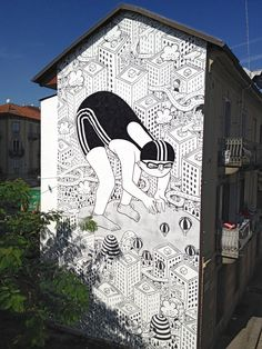 Millo, an Italian street artist creates huge murals that feature giant friendly figures navigating their way through cityscapes.