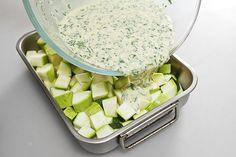 Духовку разогреть до 200 градусов. Небольшую форму для запекания смазать оливковым маслом. Кабачки нарезать небольшими кубиками и выложить в форму.