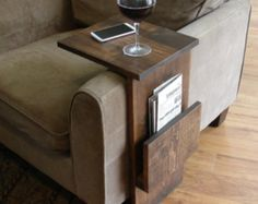 Handcrafted tray table stand with storage pocket. The perfect addition to a sofa chair in any home, apartment, condo, or man cave.  It has been sanded down, then stained and sealed with a dark walnut finish. The stand is free standing and can be used anywhere around the house.  Non-marking, non-skid rubber pads are installed on the bottom of the base. This piece does not include the accessory items as shown in the pictures.  The color of the stained wood captured in the photos might vary…