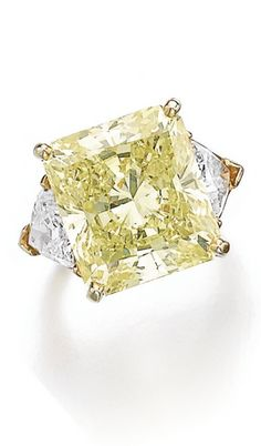 Fancy intense yellow diamond ring, Cartier The cut-cornered rectangular modified brilliant fancy intense yellow diamond weighing 19.30 carats, set between triangular near colourless diamond shoulders, size 50, signed Cartier, numbered.