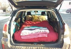 "camping bed set up in the back of a subaru outback with a kids size 5"" memory foam mattress for a month long road trip across the country"