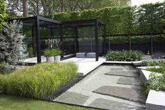 jardin moderne aménagé avec une pergola, des parterres de fleurs et de graminées d'ornement et un étang