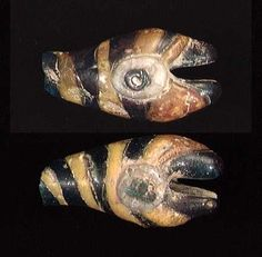"""A RARE EARLY EGYPTIAN MOSAIC GLASS SNAKE HEAD, late New Kingdom, ca. 1375-1180 BC. Opaque, blue and yellow striped mosaic glass with white and blue eyes. Very early example of Mosaic glass. 1.5"""". Flake on tip. A related snake head is known from the Amarna royal tombs."""