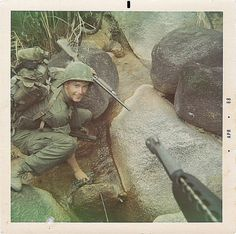 """""""Alan Allen with his Stevens 12 ga. shotgun, .45 pistol, and M-79, filling canteens(note pack and canteens); Allen carried all three weapons until he could find a replacement to pawn off the .45 pistol and the M-79. Allen thinks the M-79 is an almost..."""