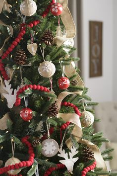 How to create a classic Christmas tree: white and red ornaments contrast with the green branches beautifully. Add natural elements like pine cones and burlap for a woodland touch! Get more holiday inspiration on our designHAPPY blog!