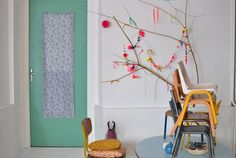 Colored pom poms decorate a branch in the home of the French stylist Aurélie Lécuyer of the blog Le Dans La.