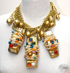 BABY YOU CAN DRIVE MY CARS: A spectacular baroque necklace composed of three 1950s Dinky Toys cars (2 Jaguar cars and a London cab) studded with cabochons and enhanced with gold leaf with various pearls and beads in glass and plastic as well as turquoise wrapped around each car with brass thread, the ensemble mounted on several metal chains, some gilt or in brass, with pearls painted gold. One-of-a-kind, Surreal Couture, New York 1978. Collection: Barbara Berger, Mexico