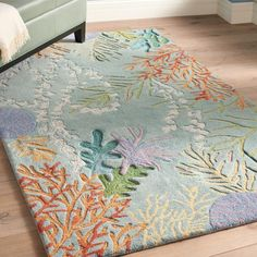 Take the plunge and add this gorgeous wool rug to your home's d. With a design like a deep sea adventure, you'll enjoy the flora and fauna a coral    reef under your feet. Hand-tifted, the skilled artisans capture the waving motion of the underwater world. Textural yarns and embroidery add to the    impactful design.            Elegant wool rug capturing the undersea world of corals and kelp                Hand-tifted with a cut and loop pile                100% Wool                Spot c...