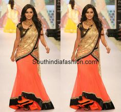Model in orange net lehenga with black sequin border, copper shimmer blouse and cream color polka dots duppatta with thin black sequins border.