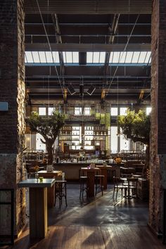 Restaurant and bar with brick walls and high exposed ceiling and sky lights.