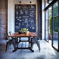 chão de cimento queimado + mesa de madeira com cadeiras pretas + parede de tijolinhos + lousa + janelões #decor #detalhes #details