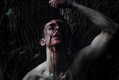 Dark blood ran down the side of his face and down his bare neck and chest. His eyes were bruised and swollen closed. Blue and green splotches covered his entire body. His hands and face were smeared with crimson. To anyone else, he'd be unrecognizable. But I knew. It was Rayne.
