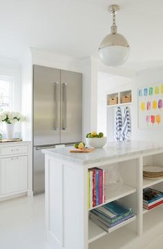 A Large Hicks Pendant hangs over an open kitchen island fitted with cookbook shelves and a gray and white marble countertop.