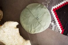 Layered rugs in nursery with olive pouf