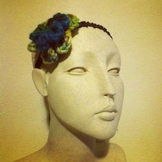 Double flower 100% bulky soft acrylic yarn in a mixed dye lot of blue, green, yellow and brown on a brown elastic headband. One size fits all. The flower is a detachable hair clip $18