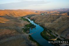 After a day of exciting desert exploration, the rushing rapids of the Kunene River lull you sleep at remote Serra Cafema, Marienfluss Conservancy, Namibia. Namib Desert, Mountain Range, Hotel Offers, Wonders Of The World, Banks, Wilderness, Lush, Stretches, Safari