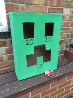 Minecraft Party Bean Bag Toss| CatchMyParty.com-Paint a cardboard box green and cut out the eyes and mouth to make a Creeper to toss bean bags in for points.