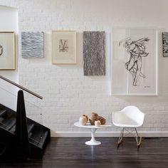 parede de tijolos a vista branca com quadros formando uma escada