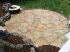 Random-cut buff flagstone patio with brick edge and natural boulder edgers. By Native Edge Landscapes in Boulder, Colorado.