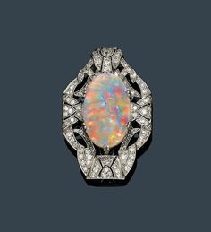 OPAL AND DIAMOND CLIP, France, ca. 1925. Platinum. Decorative, geometrically open-worked clip brooch, the centre set with 1 oval black opal of ca. 8.00 ct and set throughout with 107 single-cut diamonds weighing ca. 2.40 ct. Clip in white gold   - by Koller Auctions