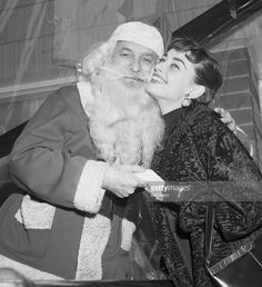 New York, NY- Audrey Hepburn, recently named the top movie star of 1953 by 'Film Daily,' gets a kiss from Santa Claus during ceremonies at the 'Heart Thrift House,' in New York Dec. 21. Miss Hepburn also tied the bow on New York's biggest Christmas package, 'The Heart Thrift House,' a model home exhibited for the benefit of the New York Heart Association.