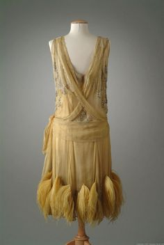 1927 Saffron yellow evening gown of silk chiffon. A criss-cross effect on the bodice is achieved with edging of rhinestones and seed pearls. Gussets on the skirt are accented with yellow ostrich feathers and beads.