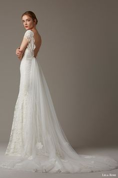 """""""The Woodlands"""" is a romantic, sophisticated gown with an embroidered lace sheath and cap sleeves. The low back is accentuated by a detachable tulle watteau train that is truly stunning. Note: This is a sample gown from a Nearly Newlywed 'preferred boutique partner.'"""