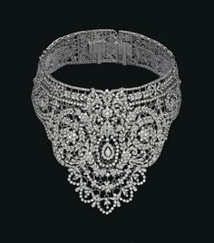 A DIAMOND BIB CHOKER NECKLACE Of oriental inspiration, with diamond-set swags, flowers, foliate scrolls and garlands on a lattice base, inner circumference 33.0 cm