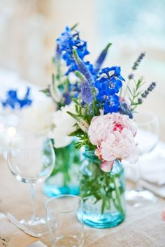 you can do just about anything with mason jars, i love this simple centerpieces for the wedding using colored jars and beautiful fresh flowers