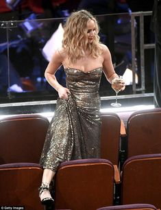 The Passengers star struggled to find her seat and was pictured flashing her leg as she lifted up her dress seemingly preparing to hop over some of the chairs