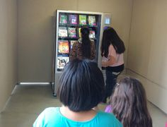 Children line up at multiple library vending machine sites.