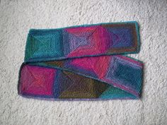 Not a boring scarf at all but a way of knitting continuous squares on two needles which look as if they've been worked in the round. Row by row instructions are given for four scarves and a sample square to practise the technique. It's easier than it looks, you only need to be able to cast on and off, knit in garter stitch and work wrapped rows and double decreases, both of which are explained in the pattern.