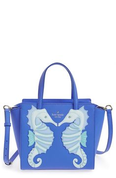 How fun and festive is this structured blue bag from Kate Spade? Vibrant appliquéd seahorses adorn one side while Its compact profile and multiple interior pockets provide room to organize the essentials.