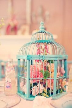 Pretty centrepiece. Have Navy/Cobalt Bird Cages with White Flowers and accents of gold or silver leaves.. Like glitter the leaves in silver or gold.  Another option is mirror bases, blue birdcage, white flowers around cage and large white candle in centre.