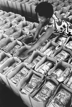 A Black Panther Party member prepares bags of food for distribution at the Black Panther Community Survival Conference, 1972.  Photo credit: Steven Kasher Gallery — in Oakland, California.
