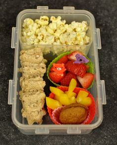 Teddy Bears Picnic bento lunch.  Popcorn, little bear sandwiches, strawberries, yellow peppers and  mini gingersnaps.